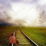 Child with teddy bear on train tracks